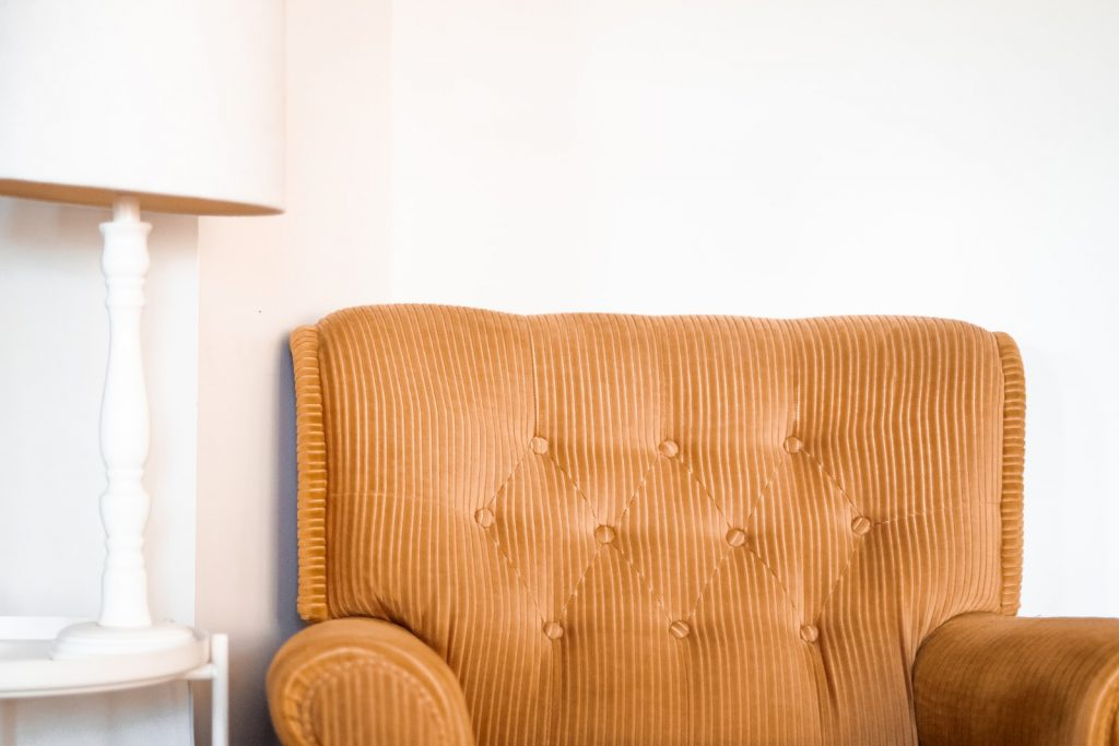 tufted brown fabric sofa chair beside white table lamp on white end table